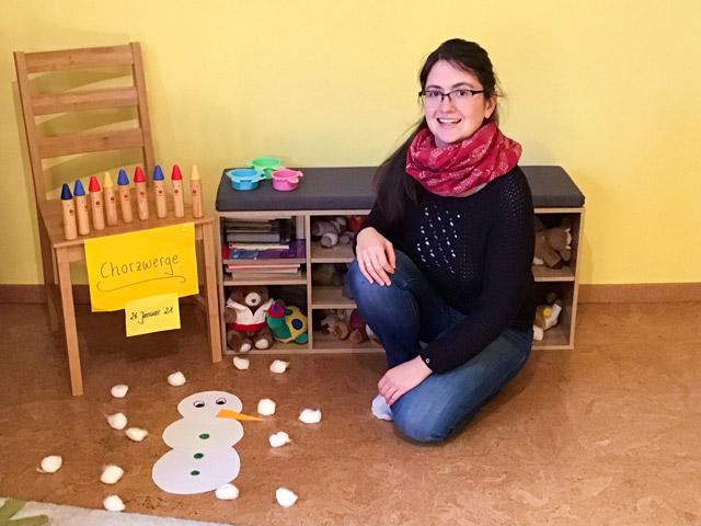 """Lehrkraft Frau Behr vor einem Stuhl mit einem Schild """"Chorzwerge"""" in der Musikschule"""