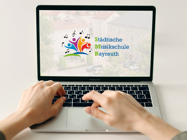 Laptop mit Händen und im Bildschirm das Musikschul-Logo –Digitaler Tag der offenen Tür – Musikschule Bayreuth